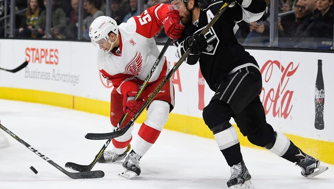 Detroit Red Wings defenseman Alexey Marchenko, left, hits Los Angeles Kings center Jeff Carter in the face as he plays the puck Jan. 5, 2017, in Los Angeles.