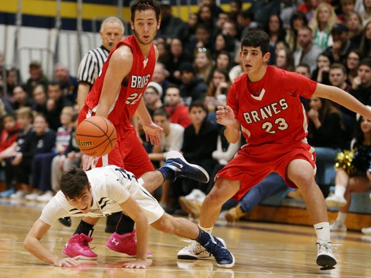 Marlboro's Ryan LaRocca goes to the ground diving for the ball as Manalapan's Anthony Shimbeno and Matan Zucker defend.  Manalapan vs Marlboro boys basketball.