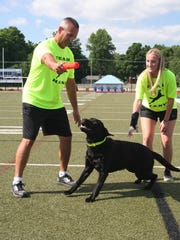 Harper Creek football coach Mike Seedorff, along with his daughter Madison, work with their dog Hank, who is one of the top dock jumping dogs in the country.