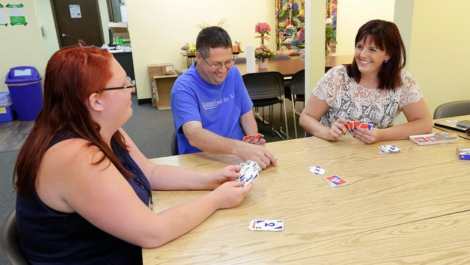 Jenna Jones and Jack Scharf play a card game with Brenda Neuman at Friendship Corner in Fond du Lac.