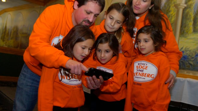 Judge Jamie Wittenberg of 45-A District Court and wife Staci look at the election results with their children Talia, 7, Maya and Brooke, 5, and Arielle, 9.
