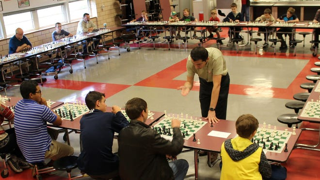 Alex Onischuk reacts to an opponent's play during Saturday's exhibition at Taylor Elementary. The grandmaster from Texas Tech played 30 opponents at once.