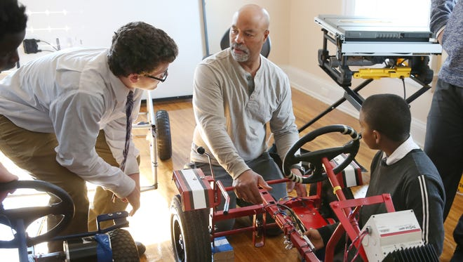 Mechanical engineer Gregory Rice, center, works with eighth graders Cullen Fingold, left, and Brandon Street, on their pair of solar powered go-carts at the University Preparatory Charter School For Young Men in Rochester Wednesday, Oct. 19, 2016.