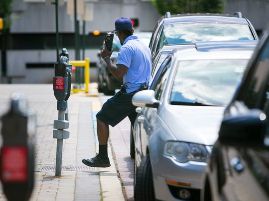 A parking enforcement officer checks the meters along North French Street in Wilmington in 2016.
