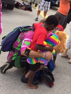 A skydiver is welcomed by waiting children.