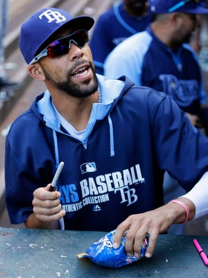 Tampa Bay Rays pitcher David Price smiles after autographing a bag of sunflower seeds for a fan after the Rays beat the Seattle Mariners 2-0 Wednesday, May 14, 2014, in a baseball game in Seattle. (AP Photo)