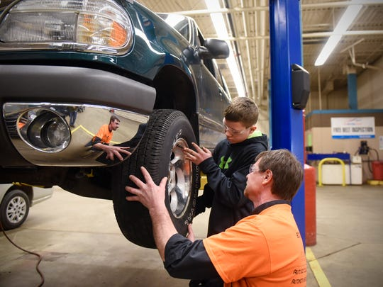 Apollo High School student Gabe Hartman and instructor Tom Hansen work together to mount a tire onto a vehicle Thursday, Feb. 9, at St. Cloud Technical & Community College in St. Cloud. Leaders in the automotive and trucking industries say they see a growing need for new talent.