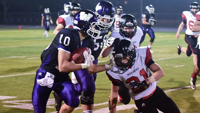 Waukee's wide receiver  Koy Schneiter (10) stiff arms Mason City's defensive back Matthew Stephens (21) after catching a pass during the first half of the game at Waukee Stadium on Friday, Oct. 24, 2014.