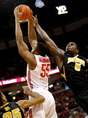 Buckeyes center Trey McDonald is defended by Iowa guard Anthony Clemmons during the first half Tuesday.