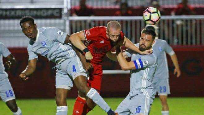 Phoenix Rising FC's Peter Ramage fights for the ball between Reno 1868 FC's Jordan  Murrell (4) and Jimmy Ockford during the first half of their USL game Saturday, May 6, 2017 in Scottsdale, Ariz.