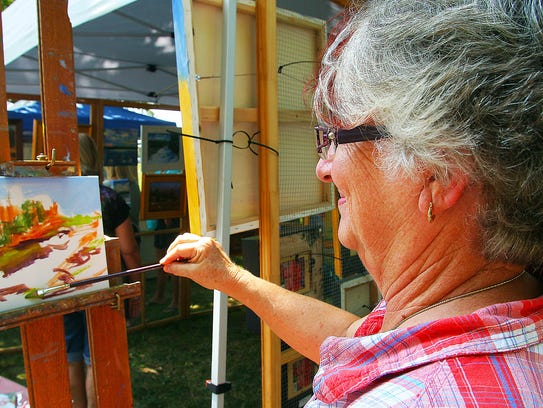 Carole Berning works on a painting at her booth at