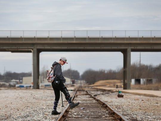 Mirenda Barrows crosses over some train tracks while