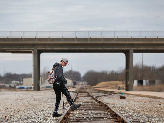 "Mirenda Barrows crosses over some train tracks while walking to the Gathering Tree to hang out with some of what she calls her ""residentially challenged"" friends on Thursday, Feb. 15, 2018. Mirenda was pregnant when she was hit by a truck while crossing the street in June 2017. She suffered extensive injuries and lost her baby."