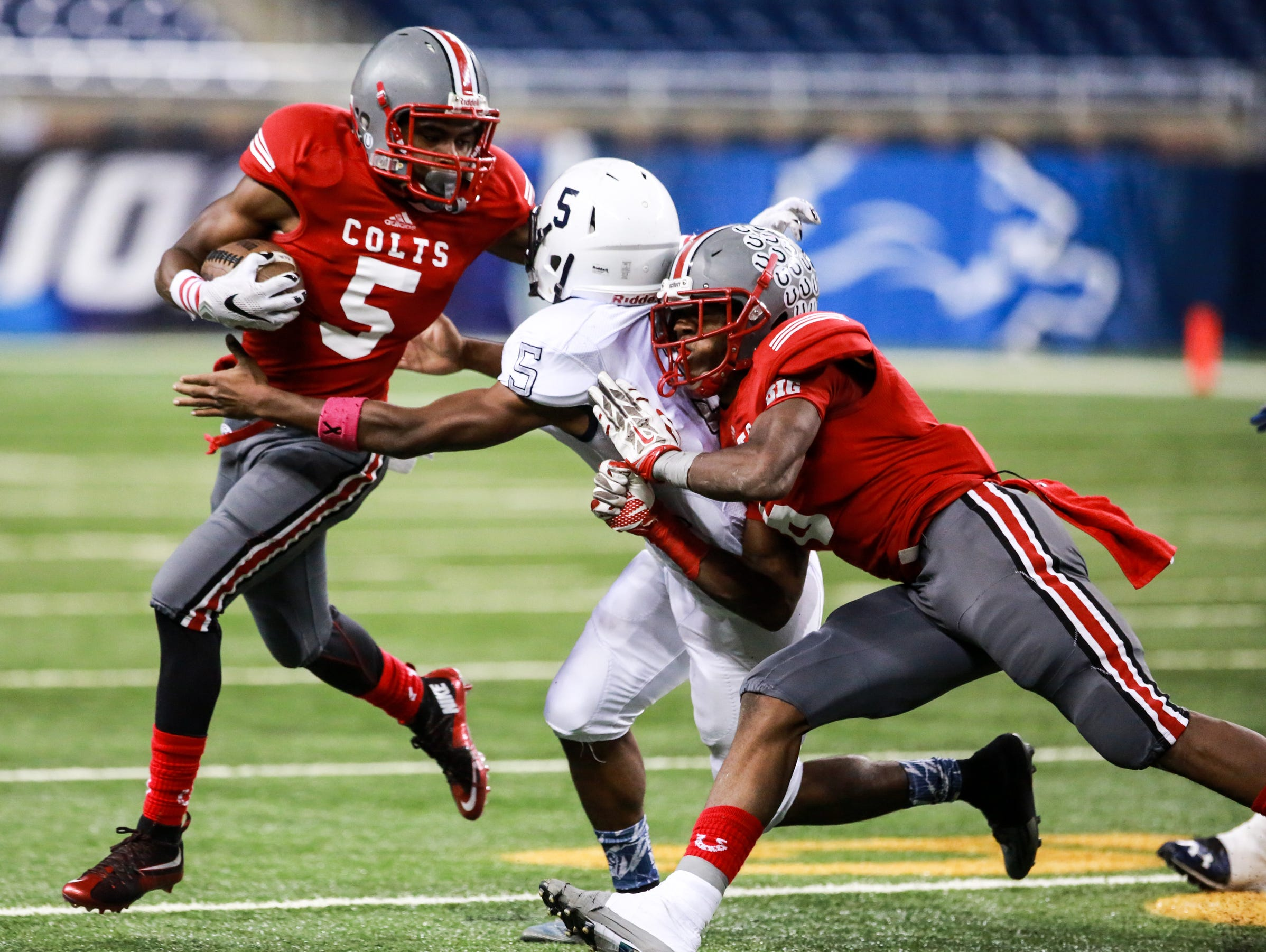 Northwestern Colts' Michael Marion runs for yardage against Central Trailblazers Lamar Perdue in the first quarter of the Detroit Public School League 2015 Football Championship at Ford Field in Detroit on Friday, Oct. 23, 2015.