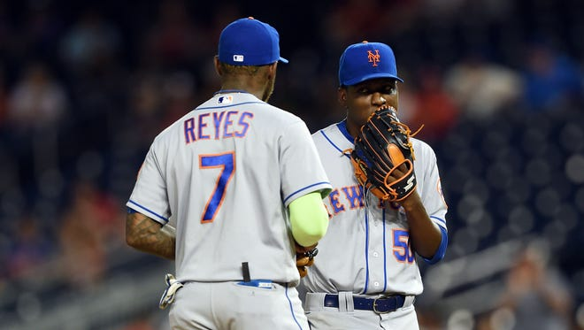 New York Mets third baseman Jose Reyes (7) speaks with starting pitcher Rafael Montero (50) during the first inning of Monday's game against the Washington Nationals on the pitcher's mound at Nationals Park.