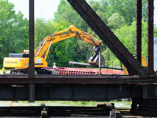 Workers remove pilings while tearing down the Porlier Street railroad bridge over the Fox River on Monday.