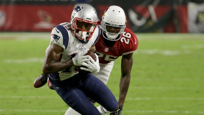 New England Patriots wide receiver Malcolm Mitchell (19) pulls down a pass as Arizona Cardinals cornerback Brandon Williams (26) defends during the third quarter on Sunday, Sept. 11, 2016.