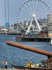 A new piling for a temporary passenger ferry dock is lifted into place on the Seattle waterfront on Tuesday.