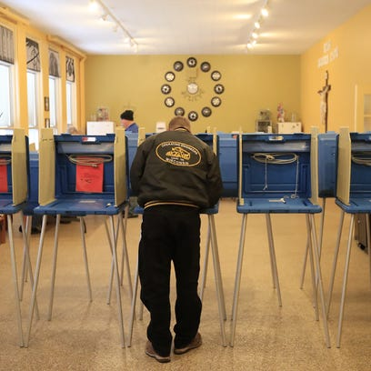 A voter fills out his ballot at St. Joseph's Parochial