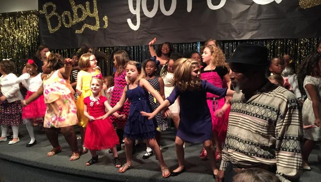 Peabody Montessori Elementary School students do a line dance on the stage of the school auditorium at a daddy/daughter dance fundraiser Thursday.