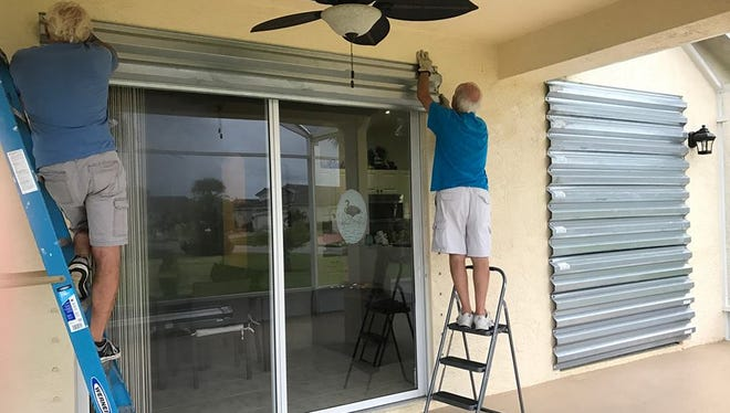 George Antropoli, right, a Rochester native living in Port St. Lucie, Florida, puts metal shutters on his sliding glass door with the help of a neighbor.
