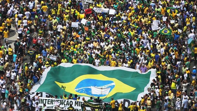 Anti-government protesters march carrying a Brazilian flag along Copacabana beach on March 15 in Rio de Janeiro.