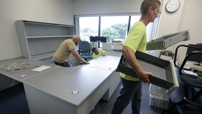 Menasha Department of Public Works employees Adam Behling, left, Nathan Schmidt, center and Aaron Langdon set up desks at the new City Hall offices on Thursday in Menasha.