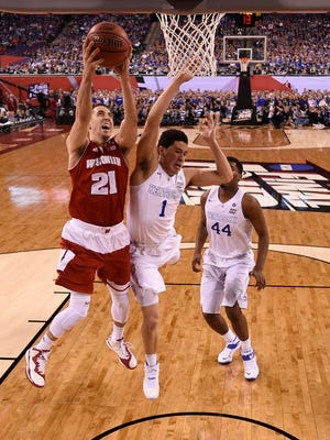 Wisconsin Badgers guard Josh Gasser (21) shoots the ball against Kentucky Wildcats guard Devin Booker (1) during the second half of the 2015 NCAA Men's Division I Championship semi-final game at Lucas Oil Stadium.