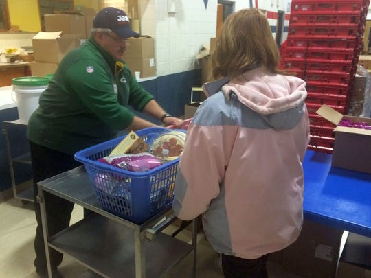 The Rev. Paul Pett, pastor at Redeemer Lutheran Church, helps a customer with her food selections during the first Ruby's Pantry distribution at the Green Bay church Monday.