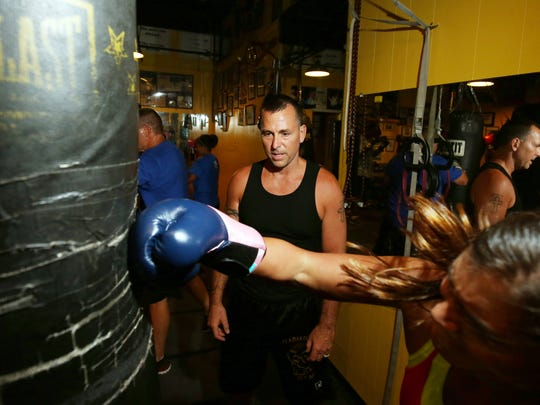 Sean Darling works with a student at Adult boxing class at Gladiator Fitness in Lacey.  F
