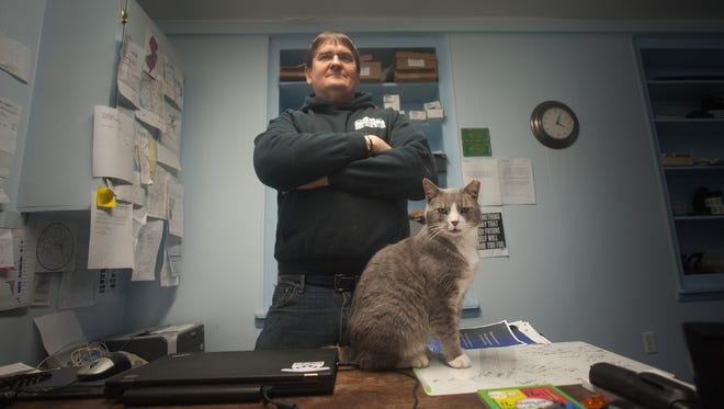 """Gary Meyer poses for a photo Thursday at his office in Millville. Meyer is the volunteer coordinator for a program Millville started in August 2012 to trap wild cats for medical treatment and then return to the outdoors. He operates a registered cat """"colony"""" at his business on Columbia Avenue in Millville. This cat also is recuperating from being shot recently."""