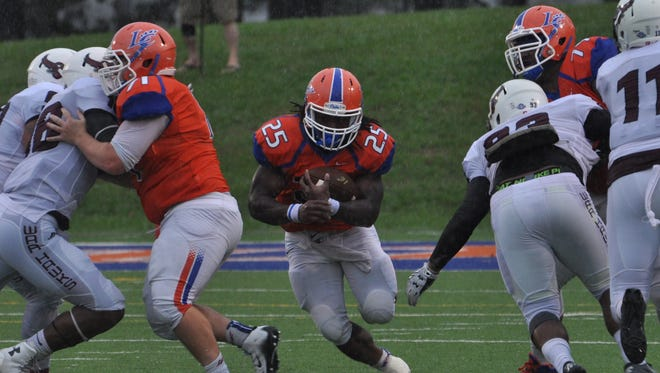 Louisiana College junior Aurren Cooksey runs through a hole against McMurry