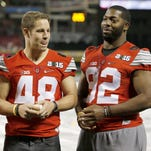 Ohio State linebacker Joe Burger, a La Salle High School alumnus, left, and defensive lineman Adolphus Washington, a Taft High School alumnus, right, are presented with the Reds Country Athletic Achievement Award ahead of the Opening Night game against the Pittsburgh Pirates, Wednesday, April 8, at Great American Ball Park. The Enquirer/Kareem Elgazzar