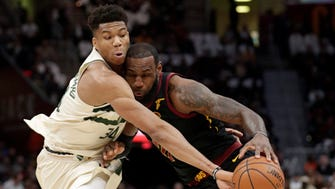 The Bucks' Giannis Antetokounmpo knocks the ball loose from the Cavaliers' LeBron James in the first half Monday in Cleveland.