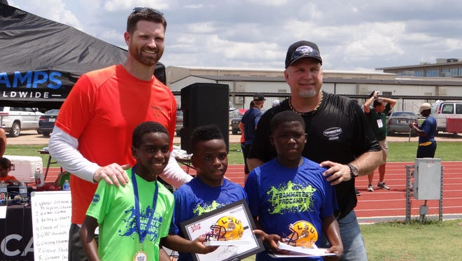 Rudy Niswanger (back left) and Garth Brooks (back right) present awards following a football/team building camp at Airline High School on Saturday.