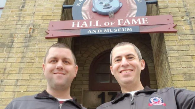 Brad Novak, left, and Phil Sklar stand in front of their National Bobblehead Hall of Fame and Museum in Milwaukee. The Guilford grads have had their best sales stretch over the past six-plus months with kind-hearted pandemic-related bobbleheads.