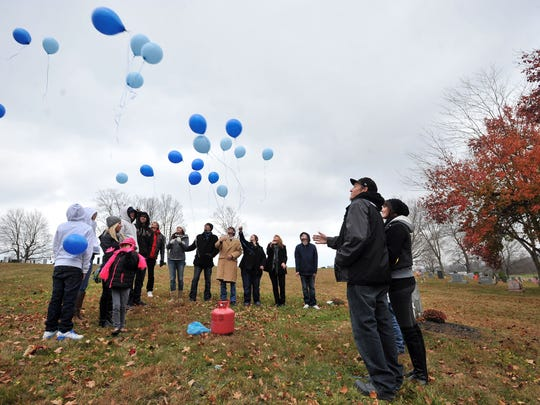 Friends and family members of Josh Barnes release balloons near his grave Nov. 13, 2014, at Maple Grove Cemetery in Lancaster.