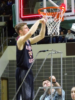 Fairfield Union senior Hayden Price cuts down the net after the Falcons defeated Miami Trace, 42-40, to win the Division II Southeast district championship.