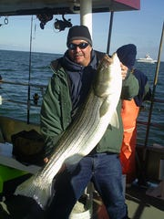 Sandar Baker, from Norristown, Pennsylvania, with a striped bass on the Sea Hunter.