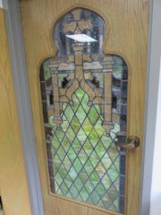 A stained glass window from the former church building is used in a door at the current church.