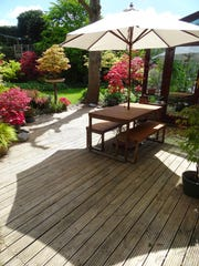 Image of garden timber-decking, table and benches with parasol umbrella