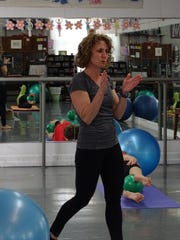Pilates instructor Laura Tyson demonstrates moves during Pilates class and then walks around to see how her students are doing.