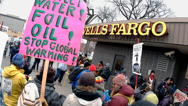FILE - In this Nov. 17, 2016, file photo, Dakota Access pipeline protesters form a circle as they demonstrate outside a Wells Fargo Bank branch in Bismarck, N.D. Opposition to the four-state Dakota Access oil pipeline has boosted efforts to persuade banks to stop supporting projects that might harm the environment or tread on indigenous rights. (Mike Mccleary/The Bismarck Tribune via AP, File)