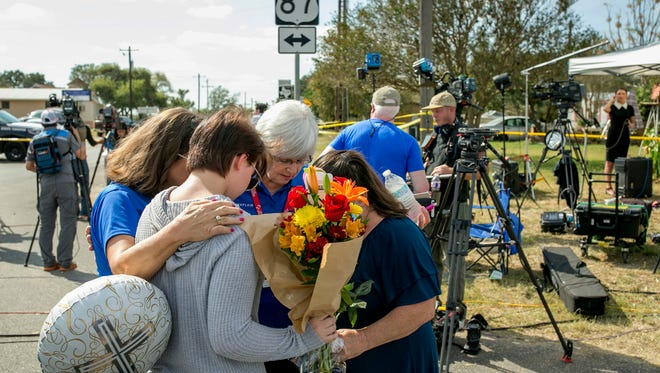 Chaplains Sharon Folsom, left, and Jeanie Tidwell, second from right, of Billy Graham Rapid Response Team, pray with Belinda McLaurin, right, and her 14-year-old granddaughter, Randi Ray Rivera, near the scene of the mass shooting at First Baptist Church in Sutherland Springs, Texas, on Nov. 7, 2017.