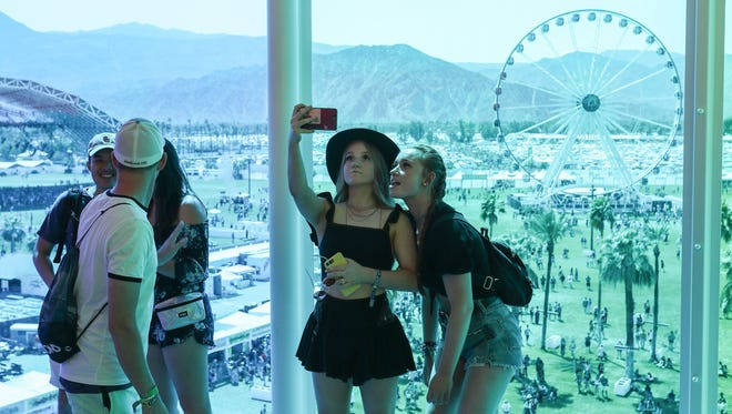 Music fans take pictures inside The Spectra art installation Friday during opening day of the Coachella Valley Music and Arts Festival at Empire Polo Club.