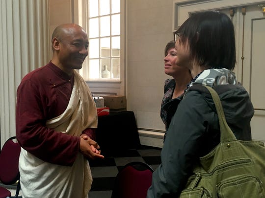 Anam Thubten speaks with two women after his presentation at the Festival of Faiths.