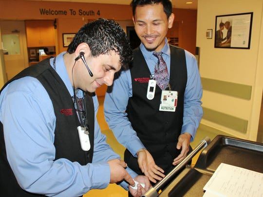 Diet aides Yazid Swailih, left, and John Paras discuss patient tray information during the cart hand-off.