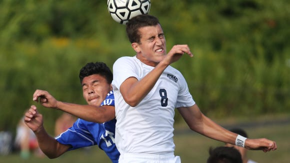 Byram Hills' Garrett Wolfe heads the ball in front of Port Chester's Kevin Umanzor during the Byram Hills vs. Port Chester boys soccer game in Armonk, Sept. 4, 2015. Byram Hills beat Port Chester 1-0.
