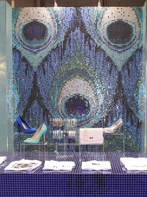 An installation designed by Capra at McCormick Place in Chicago during the 2016 Coverings trade fair showcased the creative use of mosaic tiles, featuring a stunning iridescent peacock feather.