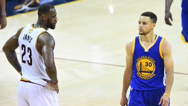 Jun 10, 2016; Cleveland, OH, USA; Cleveland Cavaliers forward LeBron James (23) and Golden State Warriors guard Stephen Curry (30) look on from the court during the fourth quarter in game four of the NBA Finals at Quicken Loans Arena. The Warriors won 108-97.